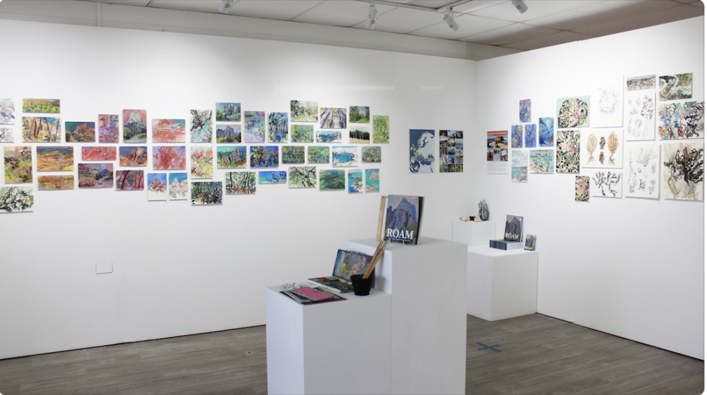 small Gouache paintings using a salon hang on two gallery walls plinth in foreground with artist supplies and book